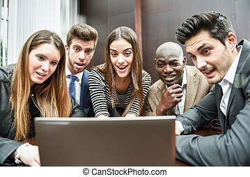 Group of multiethnic busy people looking at a laptop -...