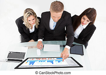 High angle view of businesspeople using desktop PC together at desk in office