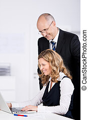 Businesspeople Using Laptop At Desk