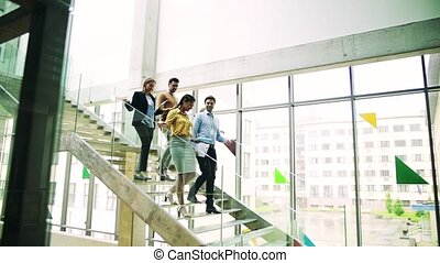 Businesspeople walking down the stairs in the modern...