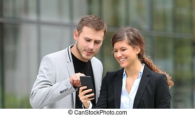 Businesspeople watching smart phone content