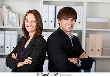Businesspeople With Arms Crossed Standing In Office