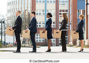Businesspeople With Boxes Standing In A Line
