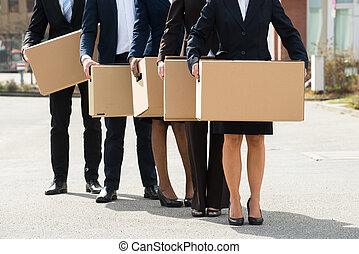Businesspeople With Cardboard Boxes Standing In A Line -...