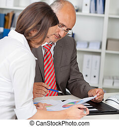 Businesspeople With Graphs In Meeting - Mature businessman...