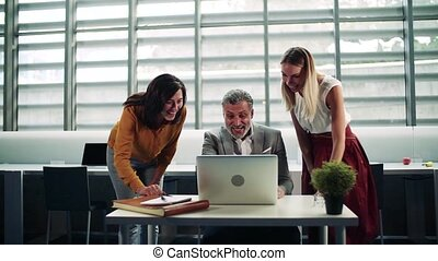 Businesspeople with laptop in office, expressing excitement....