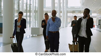 Businesspeople with suitcase using mobile phones while walking in office 4k