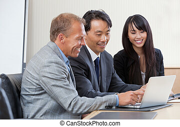 Businesspeople working on laptop - Diverse group of...