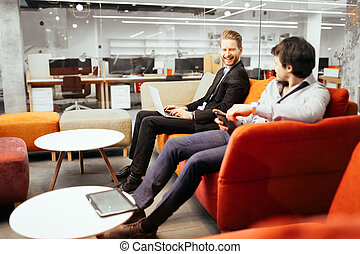Businesspeople working while looking at devices