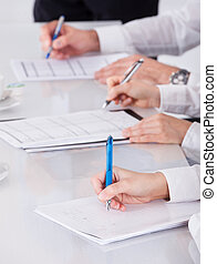 Businesspeople Writing Notes In Meeting