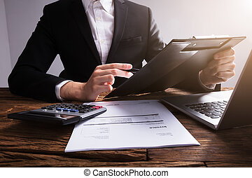 Businessperson Analyzing Document On Clipboard