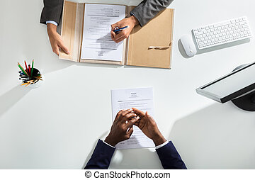 Businessperson And Candidates Hand Over White Desk
