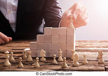 Businessperson Arranging Chess Piece On Wooden Blocks