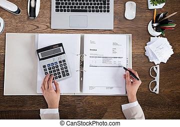 Businessperson Calculating Bill On Wooden Desk