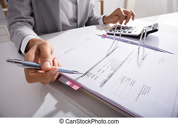 Businessperson Calculating Bills In Office - Close-up Of...