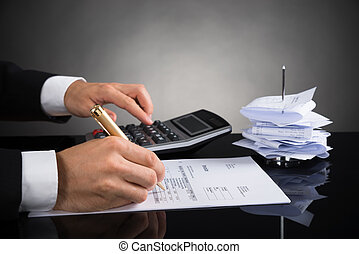 Close-up Of Businessperson Calculating Invoice With Calculator At Desk