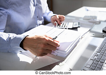 Businessperson Calculating Invoice Using Calculator At Desk