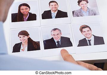 Businessperson Choosing Photograph Of Best Candidate