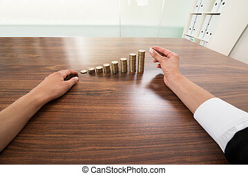 Businessperson Hand Putting Coin To Stack Of Coins