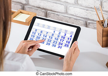 Businessperson Holding Digital Tablet With Calendar On...