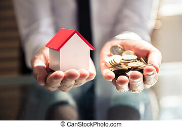 Businessperson Holding House Model And Golden Coins
