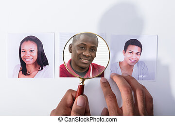 Businessperson Holding Magnifying Glass Over Applicant's Photo
