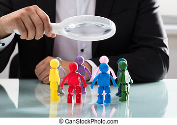 Businessperson holding magnifying glass over figures