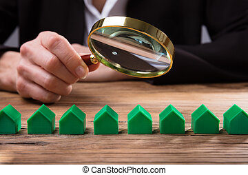 Businessperson Holding Magnifying Glass Over House Model