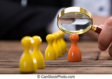 Businessperson holding magnifying glass over orange pawn