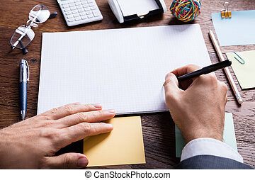 Businessperson Holding Pen On Blank Notebook