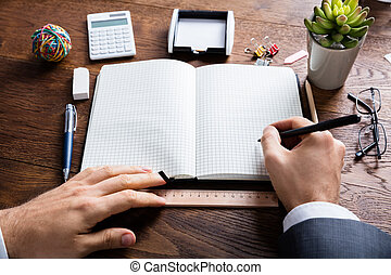 Businessperson Holding Pen On Diary