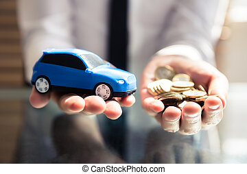 Businessperson Holding Small Blue Car And Golden Coins