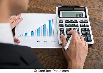 businessperson, hos, graph, og, regnemaskine, skrivebord