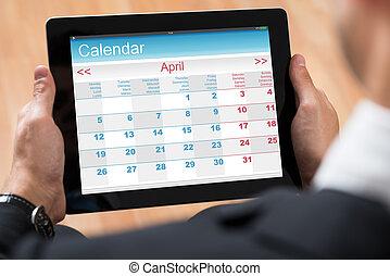 Businessperson Looking At Calendar On Digital Tablet