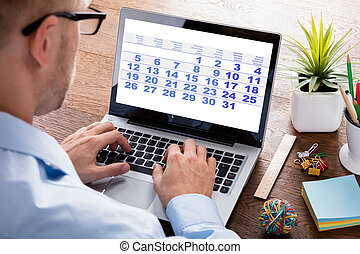 Businessperson Looking At Calendar On Laptop