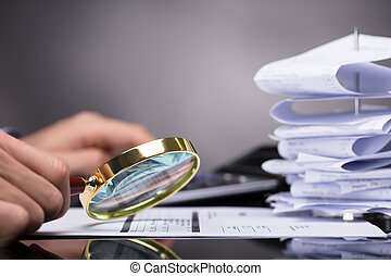 Businessperson Looking At Invoice Through Magnifying Glass
