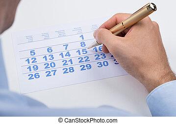 Businessperson Marking On Calendar