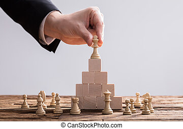 Businessperson Placing King Chess Piece On Top Of Wooden Blocks