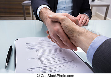 Businessperson Shaking Hand With Applicant