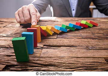 Businessperson Stopping Colorful Falling Dominos With Finger