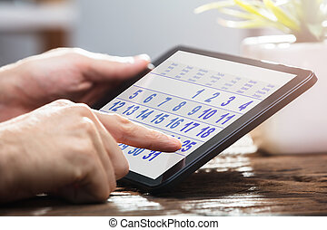Businessperson Using Calendar On Digital Tablet