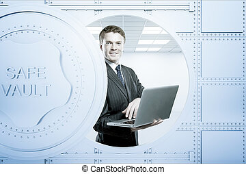 Businessperson using laptop inside bank vault