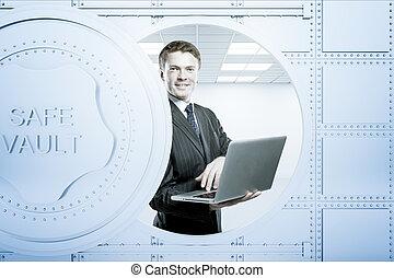 Businessperson using laptop inside bank vault