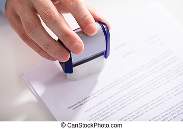 Businessperson Using Stamper On Document