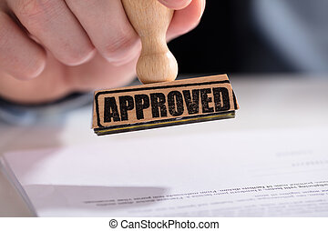 Businessperson Using Stamper On Document With Approved Text