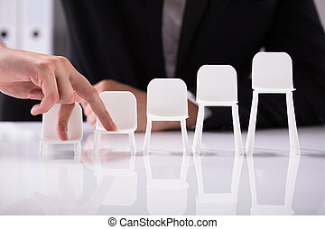 Businessperson Walking On Increasing Size Of Chairs With Finger