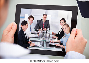 Close-up Of Businessperson Looking At Video Conference On Digital Tablet