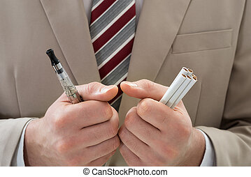 Extreme Close-up Of Businessperson Hand Holding Electronic Cigarette