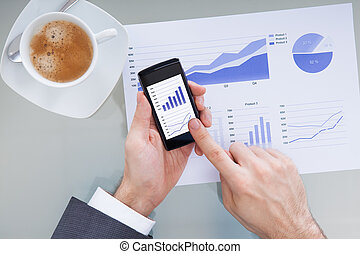 Businessperson With Mobile Phone Showing Graph