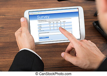 Businessperson With Mobile Phone Showing Survey Form